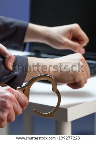 A hacker about to be handcuffed by the police - stock photo