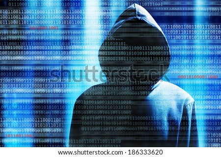 a hacker with a hood over a screen with binary code - stock photo
