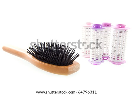 a hairbrush and curlers on a white background - stock photo
