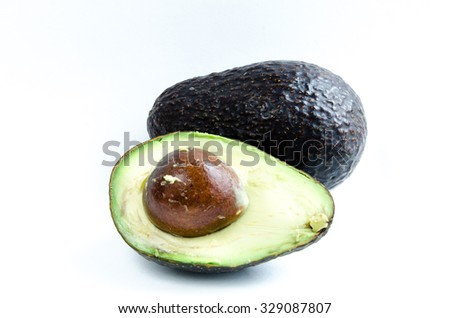 A half cut with seed and a whole organic fresh ripe avocado isolated on white background. Copy space