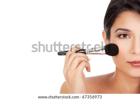 a half-face crop beauty portrait of a younf woman, applying blush on her cheecks with a blusher brush - stock photo