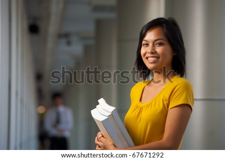 A half portrait of a cute smiling college student wearing yellow shirt in hallway of a beautiful modern campus.  Young female Asian Thai model late teens, early 20s of Chinese descent