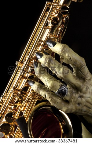 A Halloween holiday gold brass saxophone with a monster?s hand against a black background in the vertical format.