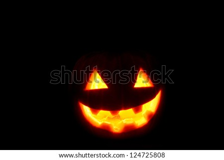 A halloween pumpkin face smiling on a black background. - stock photo