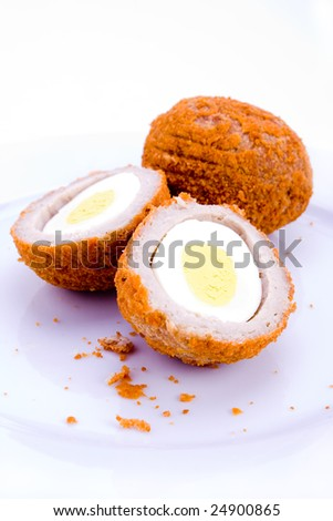 A halved scotch egg on plate on white - stock photo