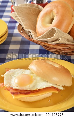 A ham, egg and cheese sandwich on a bagel on a picnic table - stock photo