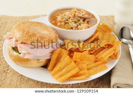 A ham sandwich on a bagel with chicken sausage gumbo and natural chips - stock photo