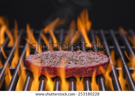 A Hamburger Cooking on a Hot Flaming grill - stock photo