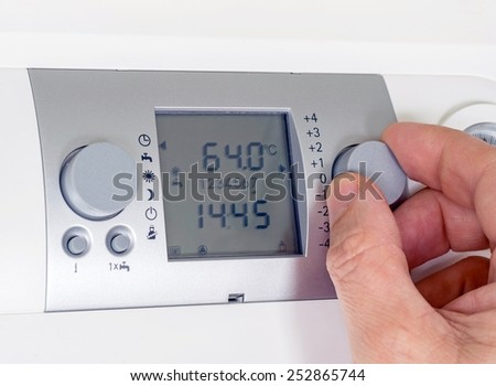 A hand adjusting the thermostat settings of a household heating system - stock photo