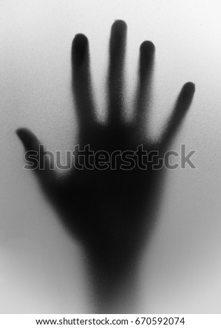 A hand behind matted glass.