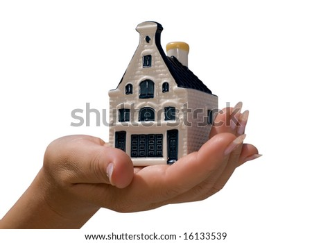 A hand bolding a toy house. Real estate, home safety, or home insurance concept. - stock photo