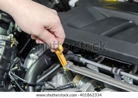 A hand Checking for engine oil on a car - stock photo