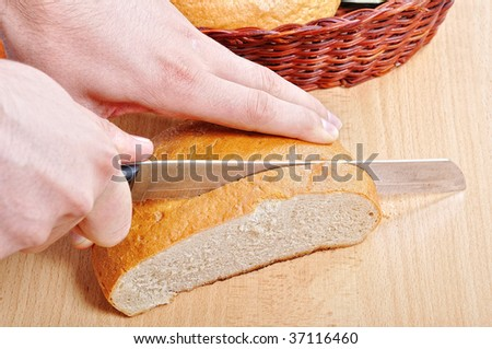 A hand cutting a piece of bread