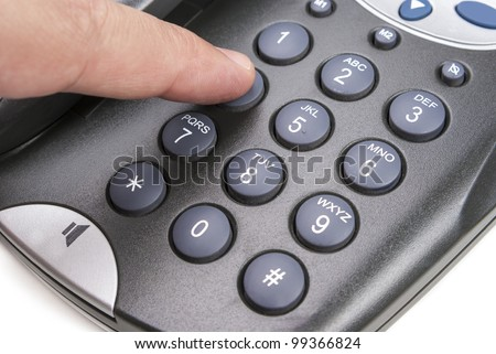 A hand dialing a call number on a telephone