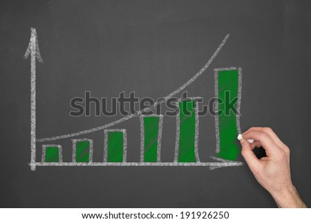 A hand drawing a business graph depicting an increase in profits on a chalkboard. - stock photo