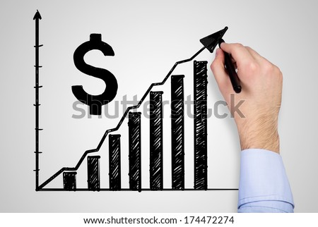 A hand drawing a dollar graph  - stock photo