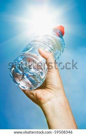 A hand holding a bottle of mineral water into the sun on a blue sky background - intentional flare. - stock photo