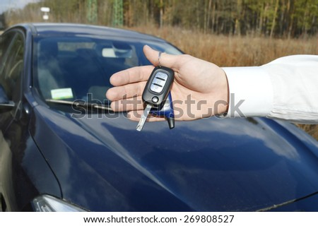 a hand holding a car's remote control pointing to the door.a man opens a machine