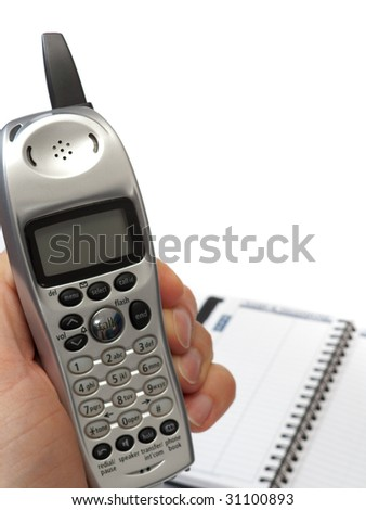 A hand holding a cordless phone, with the display facing the camera, and a blurred blank telephone directory in the background, isolated on white. - stock photo