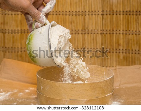 A hand holding a coup of flour.On wooden background.