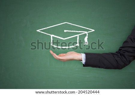 A hand holding a graduation hat  - stock photo