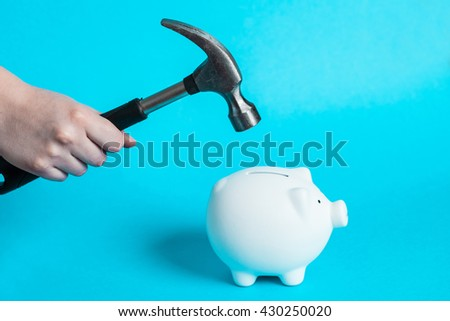 A hand holding a hammer which is raised above a white piggy bank - stock photo