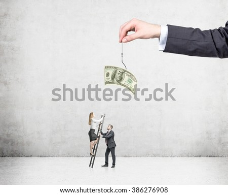 A hand holding a one-hundred dollar banknote on a thread, a young businesswoman climbing a ladder to get it, man assisting her. Concrete background. Concept of motivation. - stock photo
