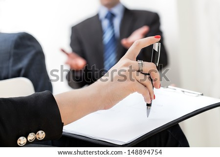 A hand holding a pen and a paper sheet at a business meeting - stock photo