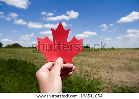 A hand holding a red, cutout shape against the sky. - stock photo