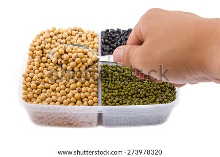 A hand holding a spoon, a lot of black bean, green beans, soybean on white background - stock photo
