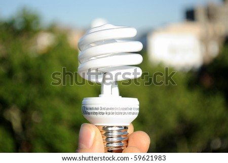 A hand holding an energy efficient light bulb against the backdrop of an urban park. - stock photo