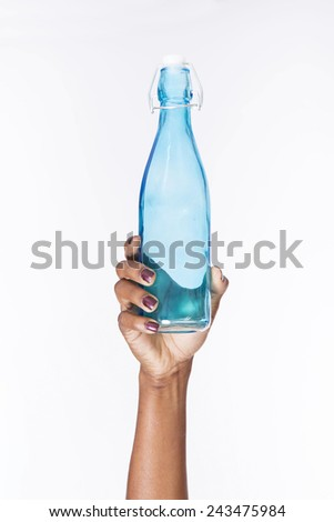 a hand holding blue bottle - stock photo