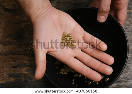 A hand holding gold nugget grains, close-up
