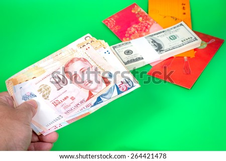 a hand holding money, focused on Singapore dollars and US dollar, one hundred dollar notes on the background  - stock photo