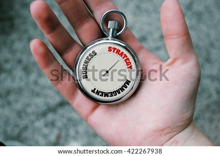 A hand holding pocket watch showing business related theme inside.
