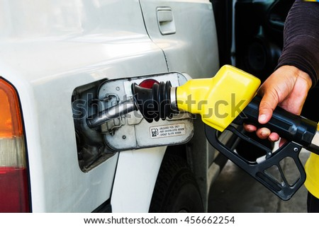 A hand holding the Yellow fuel nozzle for oil filling in the petrol station - stock photo