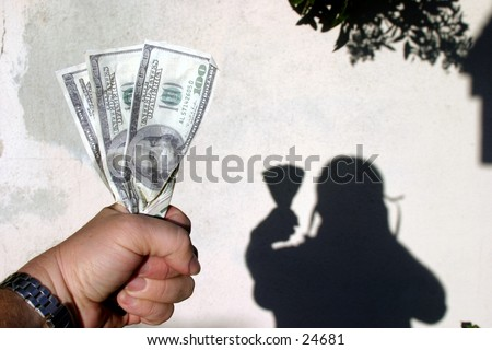 a hand holding two hundred and twenty dollars and the shadow of the holder in the background against a white stucco wall