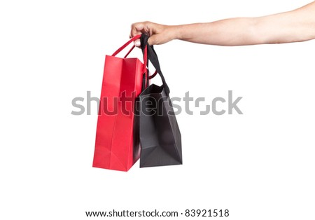 a hand holding two paper bags  on white background