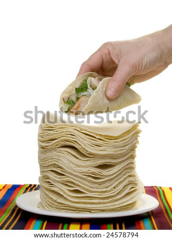 A hand holds a carnitas taco, above a huge stack of corn tortillas.