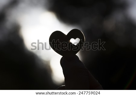 A hand holds a heart shape with a small heart shape inside it against the sun. - stock photo