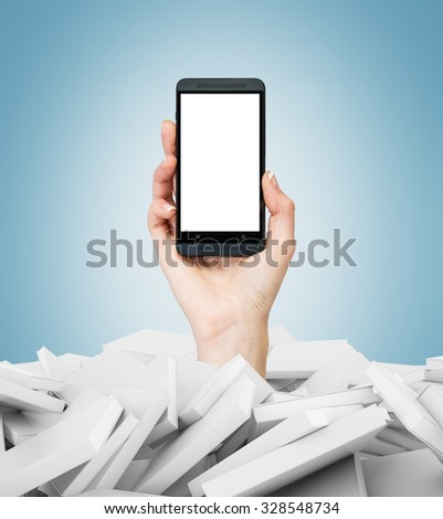 A hand holds a smartphone with white copy space screen. A heap of books with white covers. A concept of education and technology. Light blue background. - stock photo