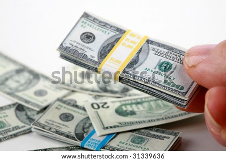 a hand holds miniature money representing the world financial crisis isolated on white - stock photo