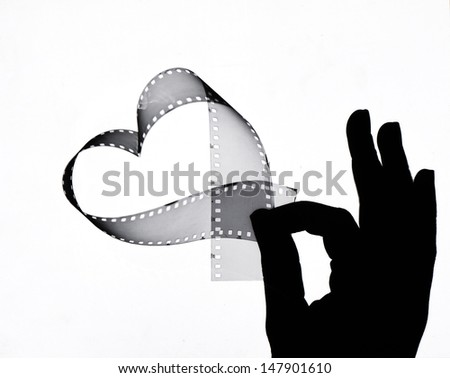 A hand holds up a heart shaped film strip - stock photo