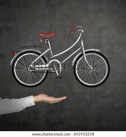 A hand in formal shirt holds a bicycle which is drawn on the black chalkboard wall. A concept of travelling. - stock photo