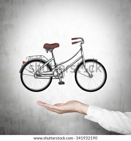 A hand in formal shirt holds a bicycle which is drawn on the concrete wall. - stock photo