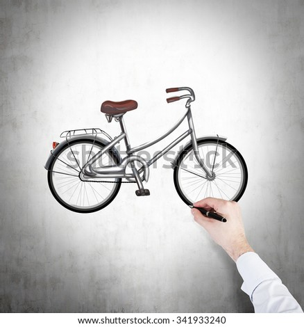 A hand in formal white shirt is drawing a colourful sketch of bicycle on the concrete wall. - stock photo