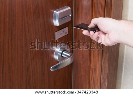 A hand inserting keycard in the electronic lock.  Closeup shoot. - stock photo