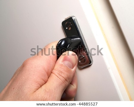 A hand is checking a white door, is the door closed? Holding a handle to a door