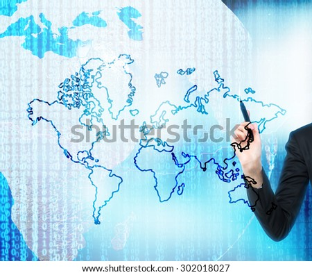 A hand is drawing the digital business world. The world map is drawn over the digital globe. Elements of this image furnished by NASA.