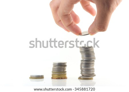 a hand is holding a coin with coins stack on a white isolated screen